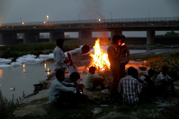 Men watch the fires of a cremation along the banks of the Yamuna River against the backdrop of the Wazirabad Barrage and floating industrial waste in May 2016.