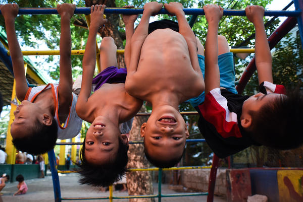 Learning to get along with others is critical for kids to succeed as adults. These youngsters are working hard at the skill on a playground in Manila.
