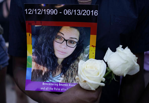 A man holds a portrait of Amanda Alvear at a vigil for the victims of the Pulse nightclub shooting, on Monday evening at the Dr. Phillips Center for the Performing Arts in Orlando, Fla.