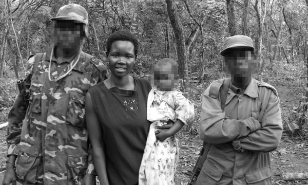The picture was taken in 2006 in the Democratic Republic of Congo, after Evelyn Amony was rescued. Holding her youngest daughter, she was at a meeting to negotiate with members of the Lord's Resistance Army. The two men, who had also been abducted, are her relatives. The faces of the men and baby are blurred to protect their identities.