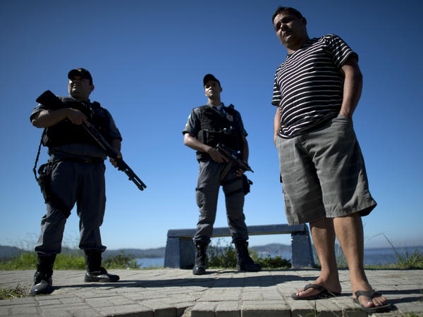 Alexandre Anderson, president of a fishermen's association, stands near Guanabara Bay, guarded by two policemen, in 2012. He is under federal protection for his role in supporting the fishermen. Fellow fishermen have been killed or have disappeared. He says they have been targeted for opposing industrial projects that pollute the bay.