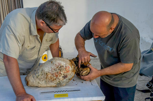 Project co-directors Brendan Foley and Theotokis Theodoulou inspect the torpedo-shaped lead cylinder recovered from the Antikythera shipwreck.