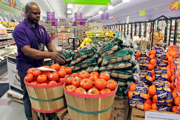 Produce manager Nate Sumpter arranges fresh fruits and vegetables at Fare and Square in Chester, Pa.