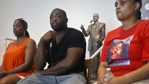 Delrawn Small's companion Zaquanna Albert, left, and his brother Victor Demsey, center, and Cynthia Howell, right, an advocate with Families United for Justice, an organization made up of families affected by police killings, attend a news conference Thursday July 14, 2016 in New York.