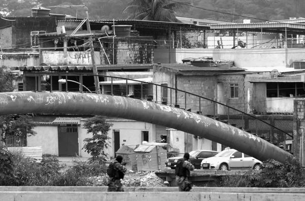 Paramilitary police monitor a checkpoint on a bridge in the City of God<em> favela</em> on July 21.
