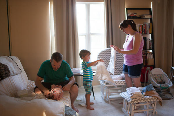Mike Cruse changes his daughter Olivia's diaper, while his 4 year-old son Benjamin and wife, Stephanie, fold laundry in their home in Alexandria, Va. Mike went back to work less than two weeks after Olivia was born.