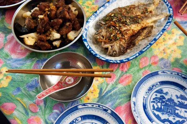 Plates of drunken pork ribs and deep-fried yellow croaker with savory soy sauce fill the dining table of Ni's home in New York City.