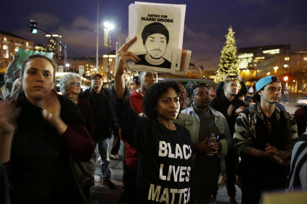 LaJoy Crenshaw, center, holds a picture of Mario Woods during a demonstration outside of city hall, in December 2015.
