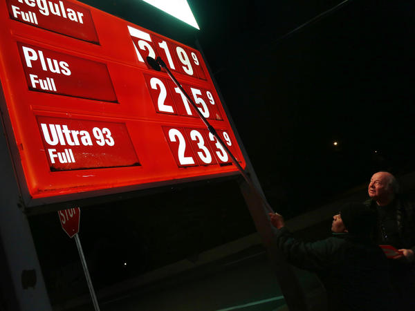 Gazi Alam (left) changes the price on a sign as Leon Balagula looks on at a Sunoco station early Tuesday in Fort Lee, N.J., following a jump in the state gas tax.