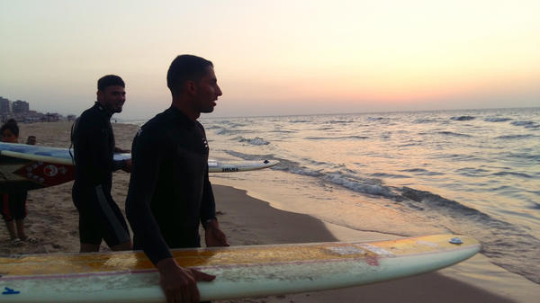 Ali Erheem (center) and his friend Tareg Naem get ready to plunge into the water at sunset in the Gaza Strip. They are members of an informal group of friends called the Gaza Surf Club, which was featured in a German documentary this year.