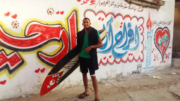 Ali Erheem, 25, poses next to graffiti on the front of his family's house in the Gaza Strip. Erheem is a member of the informal Gaza Surf Club. His painted his secondhand surfboard to look like a Palestinian flag.