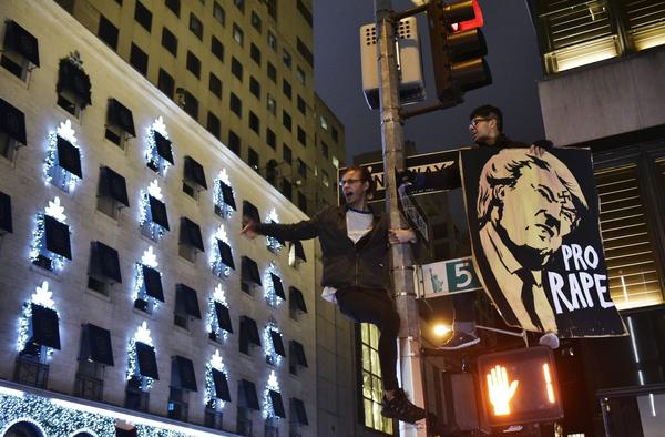 Protesters shout slogans from a lamppost during in a demonstration on Fifth Avenue across from Trump Tower on Wednesday, after Donald Trump was elected to be the next president of the U.S.