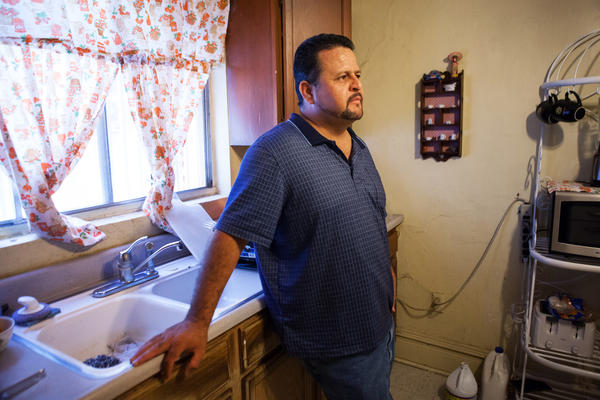 Palma stands in the kitchen of his family's home. Getting the paperwork to prove his citizenship while he was in jail was hard — he didn't have money to call his mother, so he was forced to send letters asking her for documents.
