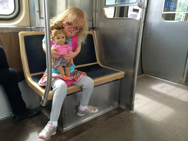 "Dominika Tamley and her doll ""Isebelle"" ride the train together in Chicago. Like Dominika, Isebelle has a hearing aid. ""She's like a mini-me,"" Dominika says."