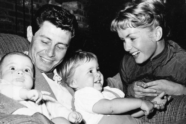 Singer Eddie Fisher and actress Debbie Reynolds cuddle their two children, 4-month-old Todd (left) and 19-month-old Carrie, in 1958.