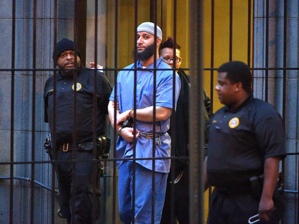 Officials escort Adnan Syed from the courthouse in Baltimore on Feb. 3 after the first day of hearings for a retrial. A judge granted the new trial, but on Thursday he denied Syed's motion to be released while he waits for the retrial.