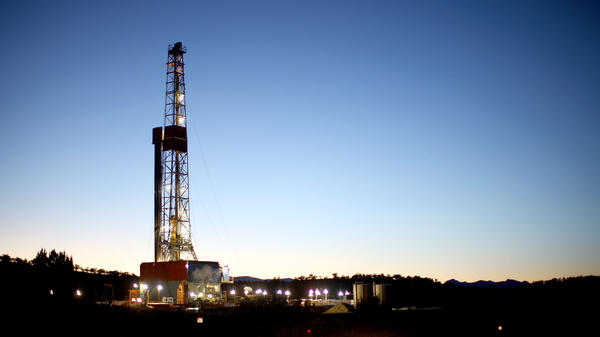A natural gas drilling rig's lights shimmer in the evening light near Silt, Colo. Methane is the main component of natural gas, and studies show some methane escapes from leaky oil and gas operations.
