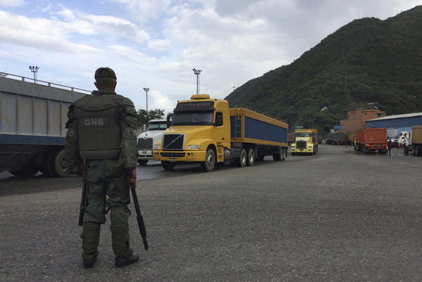 A Venezuelan soldier watches over cargo trucks leaving the port in Puerto Cabello, which handles the majority of the country's food imports. Across the chain of command, from high-level generals to the lowest foot soldiers, military officials are using their growing power over the food supply to siphon off wealth for themselves.