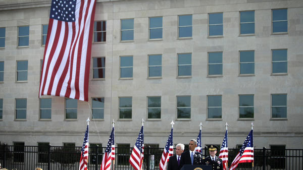 President  Obama speaks as Secretary of Defense Chuck Hagel (left) and Chairman of the Joint Chiefs Gen. Martin Dempsey (right) listen during a ceremony to mark the 13th anniversary of the Sept. 11 terrorists attacks at the Pentagon Memorial on Sept. 11, 2014, in front of the Pentagon in Arlington, Va.