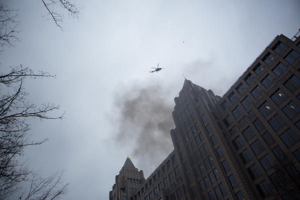 A helicopter flies by as smoke rises from a trash fire on K Street, between 13th and 14th Streets, near Franklin Square.