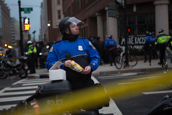 A police officer takes a break to eat a snack while protestors remain peacefully detained in the background.