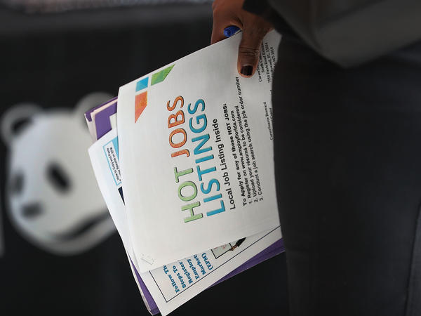 A woman holds a pamphlet announcing jobs listings during the JobNewsUSA job fair at the BB&T Center in Sunrise, Fla., in November 2016.