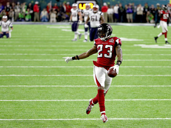 Falcons defensive back Robert Alford scores an 82-yard touchdown after picking off a pass by Patriots quarterback Tom Brady. The score gave the Falcons a daunting lead.