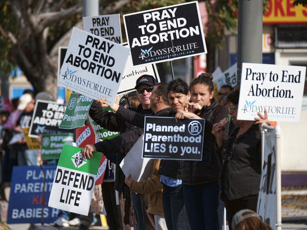 Protesters display their signs outside a Planned Parenthood health center in Los Angeles on Saturday. Together with protesters in other cities across the U.S., they gathered to demand the organization be stripped of its federal funding.