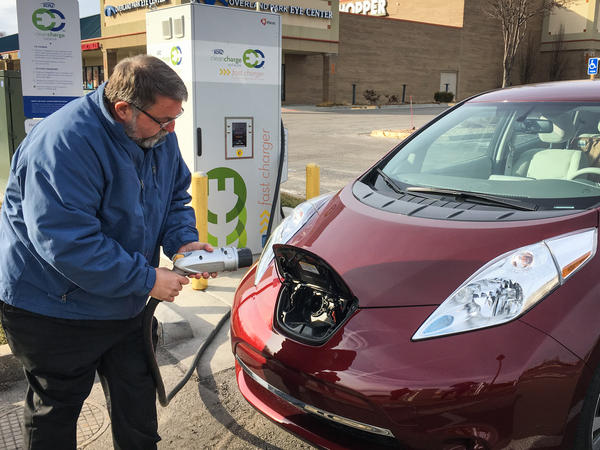 Larry Kinder, founder and CEO of LilyPad EV, gets ready to charge his Nissan Leaf at a fast-charging station at the Rosana Square Shopping Center in Overland Park, Kan.