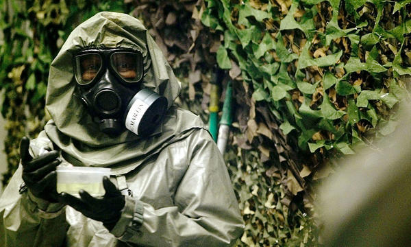 An instructor at Fort Leonard Wood, Mo., carries VX nerve agent inside a special chamber used for training in 2003.