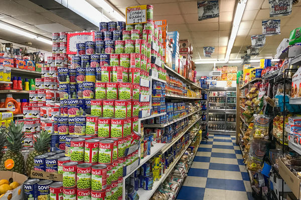 Canned beans and bags of rice line an aisle at A & M Supermarket, a large bodega in the Bronx.