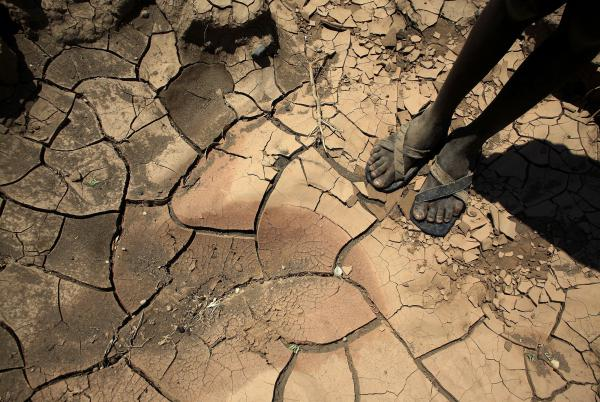 A boy from a tribe in Northern Kenya stands on a dried-up river bed.