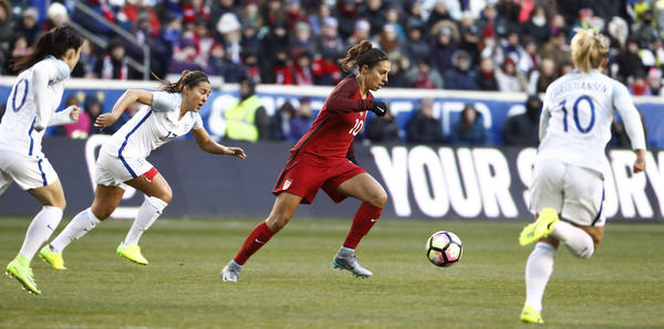 United States midfielder Carli Lloyd (center) moves the ball upfield against England during the first half of a SheBelieves Cup match on March 4 in Harrison, N.J. England won the match, 1-0.