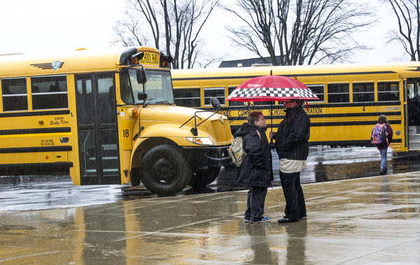 Eminence Jr.-Sr. High School Principal Corey Scott (right) chats with a student in the rain at the end of the day.