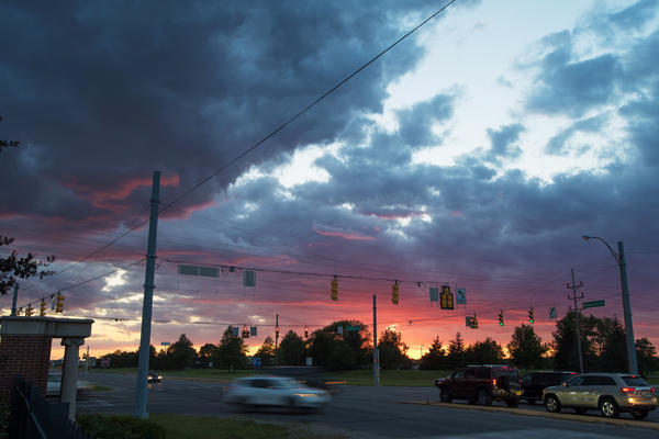 Cars drive through Muncie at dusk.