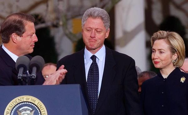President Bill Clinton get applause from Vice President Gore as first lady Hillary Clinton looks on outside the Oval Office after the House of Representatives voted to impeach the president on Dec. 19, 1998.
