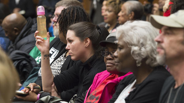 Jessica Owens holds up a baby bottle of water from her home in Flint, Mich., while attending a hearing on Capitol Hill about Flint's water crisis.