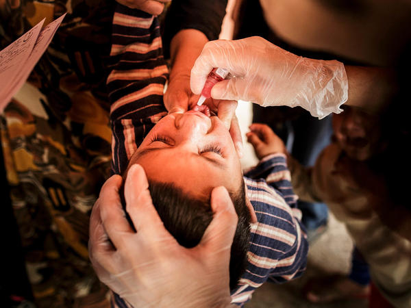 Nurses give the oral polio vaccine to a Syrian child in a refugee camp in Turkey. The oral polio vaccine used throughout most of the developing world contains a form of the virus that has been weakened in the laboratory. But it's still a live virus.<em></em>