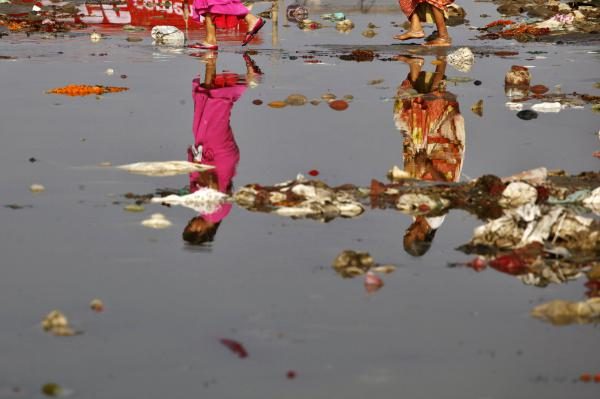 Indian Hindu devotees, reflected on the water, cross the polluted Ganges River at Sangam, the confluence of the Ganges, Yamuna, and the mythical Saraswati River, in Allahabad, India. Uttarakhand's Court conferred rights on the Yamuna when it granted rights to the Ganges.