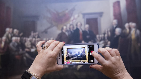 A tourist takes a photo of John Trumbull's Declaration of Independence painting in the Capitol Rotunda on June 28, 2017.