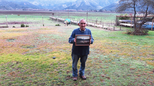 Fernando Rojas has spent his life living by a large lake in central Chile. About seven years ago it began to shrink, and now most of the water is gone. He holds a photo taken when the lake was full.
