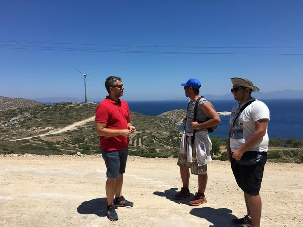 Stathis Kontos, who works for the Tilos municipality, talks to two tourists about the clean energy project after they spot the wind turbine in the distance.