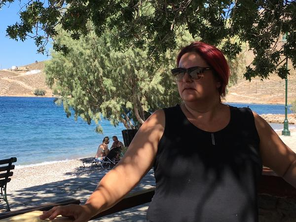 "Tilos Mayor Maria Kamma sits outside a seaside cafe. ""We wanted to evolve from simply a green island into a clean-energy island,"" she says. ""We wanted to do something substantive."""