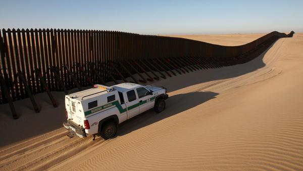 A Border Patrol vehicle patrols a section of the U.S.-Mexico border fence near Yuma, Ariz.