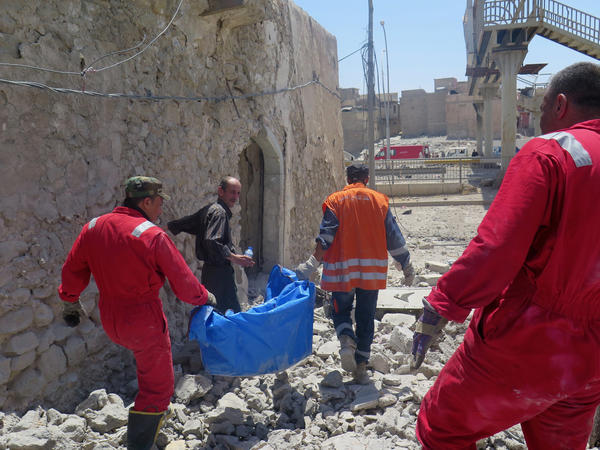 Bashar Abdul Jabar walks alongside civil defense workers as they carry his son's body. After an airstrike, their home's concrete blocks fell on 15-year-old Ahmed's legs, preventing him from escaping with the rest of the family.
