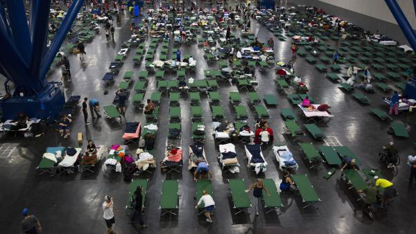 Evacuees fill up cots Monday at the George Brown Convention Center in Houston, which has been turned into a shelter run by the American Red Cross to house victims of the high water from Hurricane Harvey. Experts say it's best to donate money, not items or services, to trusted charitable organizations after a disaster — and to keep long-term needs in mind.