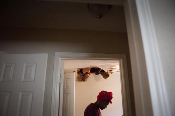 Teniya Brewer walks through Pauline Simpson's home looking at the water damage.