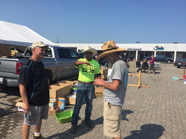 Epi Mungui (center) has been working in a strip center parking lot in his hometown of Orange, Texas, to get donations of food, water and clothing to flood victims.
