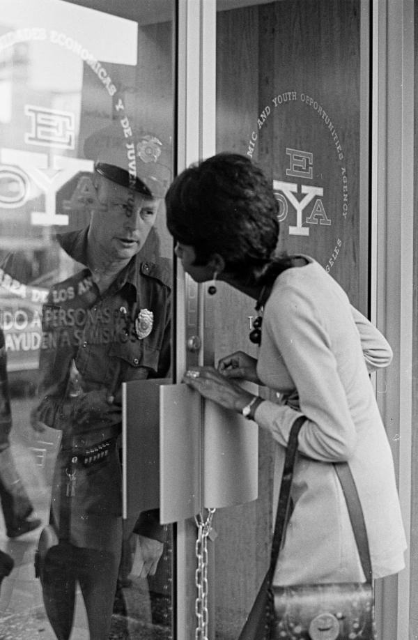 <em>A woman outside the locked Economic and Youth Opportunities Agency exchanges glances with a police officer inside. </em>Circa 1973.<em> </em>