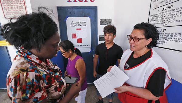 A Red Cross volunteer at a full shelter in Miami on Friday points out shelters with availability.